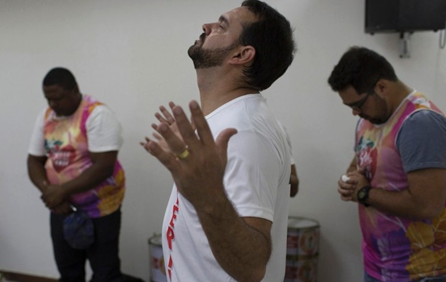 "In this Feb.19, 2017 photo, Alexandre Cunha, master of the percussion band, prays before his performance with the musicians of the Sou Cheio de Amor or ""I am Full of Love"" block party during a service at the Attitude Baptiste Church in Rio de Janeiro, Brazil. Participating in Carnival is not unheard of for evangelicals, some of whom organize street parties and use the event to recruit church members. (AP Photo/Leo Correa)"