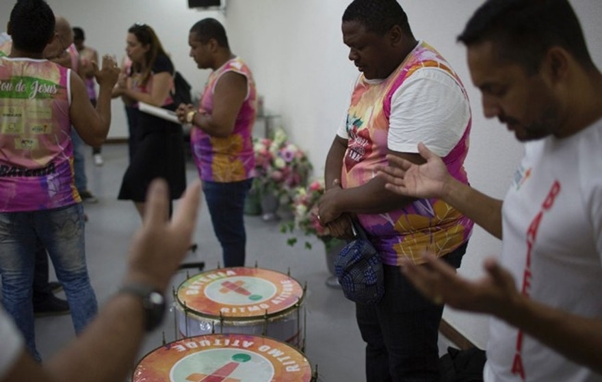 "In this Feb. 19, 2017 photo, musicians of the Sou Cheio de Amor or ""I am Full of Love"" block party pray before they perform during a service at the Attitude Baptiste church in Rio de Janeiro, Brazil. Evangelicals have enjoyed a growing role in politics in Brazil. (AP Photo/Leo Correa)"