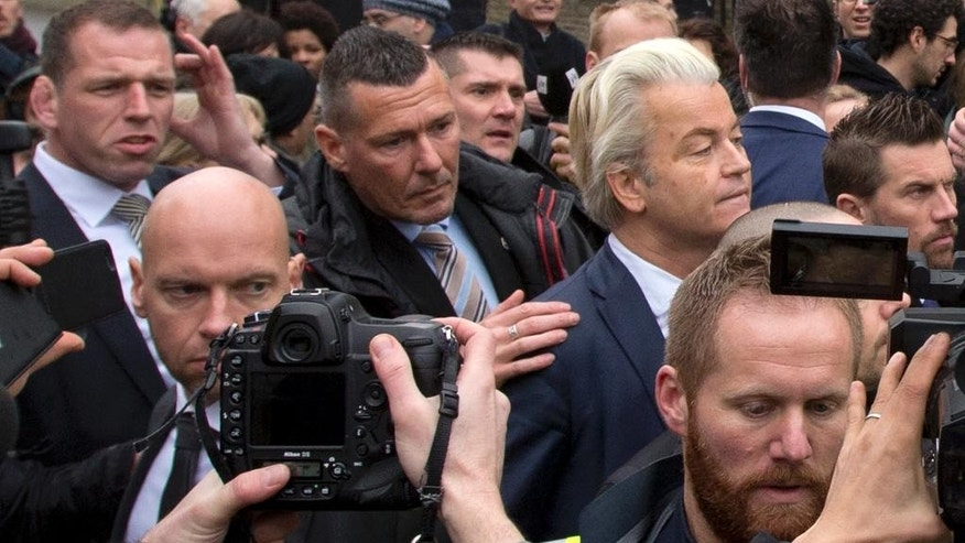 In this Saturday Feb. 18, 2017, image firebrand int-islam lawmaker Geert Wilders, right, is protected by police and security officers during an election campaign stop in Spijkenisse, near Rotterdam, Netherlands. Wilders said Thursday Feb. 23, 2017, that he will suspend his election campaigning in the wake of a scandal centering on a Dutch security official responsible for protecting the anti-Islam lawmaker. (AP Photo/Peter Dejong)