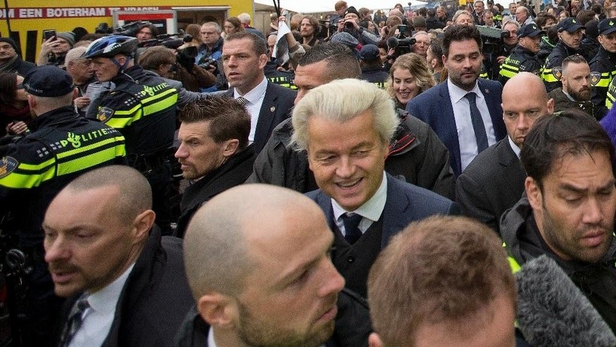 In this Saturday Feb. 18, 2017, image firebrand int-islam lawmaker Geert Wilders, center, is protected by police and security officers during an election campaign stop in Spijkenisse, near Rotterdam, Netherlands. Wilders said Thursday Feb. 23, 2017, that he will suspend his election campaigning in the wake of a scandal centering on a Dutch security official responsible for protecting the anti-Islam lawmaker. (AP Photo/Peter Dejong)