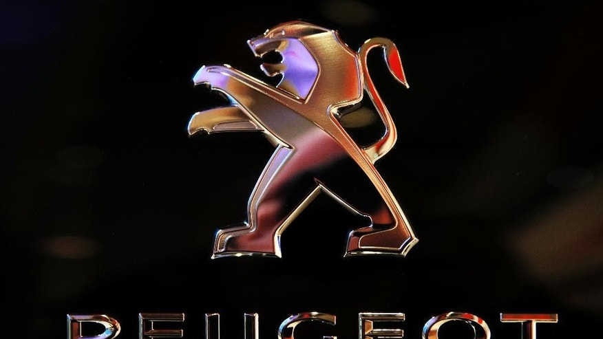 The logo of French carmaker Peugeot is pictured during the presentation of the company's 2016 full year results, in Paris, Wednesday, Feb.22, 2017. French carmaker PSA Group saw its profits jump last year and is giving dividends for the first time since 2011, burnishing its image as it weighs a buyout of General Motors' money-losing European operations. (AP Photo/Christophe Ena)