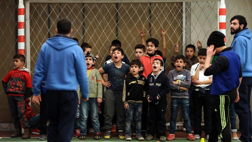 In this picture taken on Sunday, Feb. 19, 2017, Syrian refugee boys scream as they attend a soccer training session at a private sports club, southern Beirut, Lebanon. Every Sunday the gymnasium in Beirut echoes with the shouting and laughter of dozens of children, mostly Syrian refugees enjoying a rare escape from a grim and cloistered life in exile. The Sport 4 Development program, run by the U.N. children's agency, aims to bring 12,000 children, mostly Syrian refugees, to blacktops and turf pitches this year to teach the basics of soccer and basketball, and to ease the pain of war and displacement. (AP Photo/Hussein Malla)