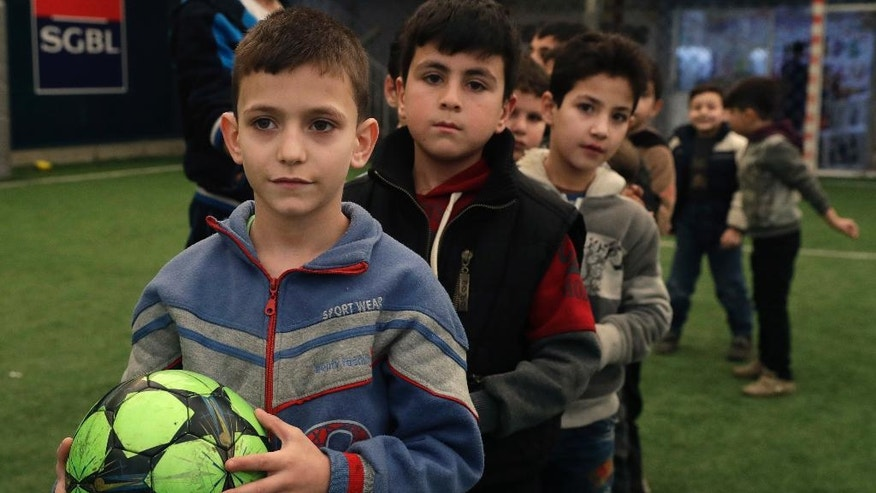 In this picture taken on Sunday, Feb. 19, 2017, Syrian refugee boys attend a soccer training session at a private sports club, southern Beirut, Lebanon. Every Sunday the gymnasium in Beirut echoes with the shouting and laughter of dozens of children, mostly Syrian refugees enjoying a rare escape from a grim and cloistered life in exile. The Sport 4 Development program, run by the U.N. children's agency, aims to bring 12,000 children, mostly Syrian refugees, to blacktops and turf pitches this year to teach the basics of soccer and basketball, and to ease the pain of war and displacement. (AP Photo/Hussein Malla)
