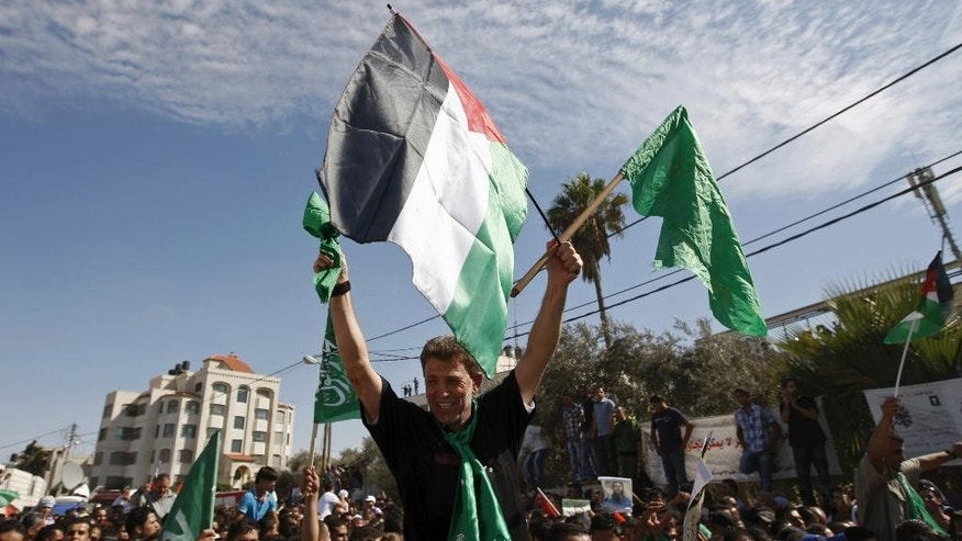 File - In this Tuesday, Oct. 18, 2011 file photo, Hamas militant Nael Barghouti waves a green Islamic flag and a Palestinian flag to the crowd after arriving in the West Bank city of Ramallah. after he was released in exchange of an Israeli soldier held by Hamas. Hundreds of other Palestinian prisoners were also released in this exchange. A Palestinian activist says an Israeli court ordered Barghouti to complete his life sentence, At the time of the exchange, Nael Barghouti had served 33 years for participating in the kidnapping and killing of an Israeli soldier, making him one of the longest-held Palestinians. (AP Photo/Majdi Mohammed, File)