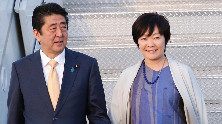 FILE - In this Feb. 10, 2017, file photo, Japanese Prime Minister Shinzo Abe and his wife Akie Abe step off of Air Force One as they arrive in West Palm Beach, Fla. An endorsement by Akie of a new elementary school run by a man with ultra-nationalistic views has been removed from the school's website amid an escalating controversy over the low price the school paid for government land. Japanese media reported that the state property in Osaka, western Japan, was sold in 2016 for 134 million yen ($1.2 million), one-seventh of its appraised price. Abe denied on Feb. 17, 2017, he or Akie had any influence over the land deal. (AP Photo/Wilfredo Lee, File)