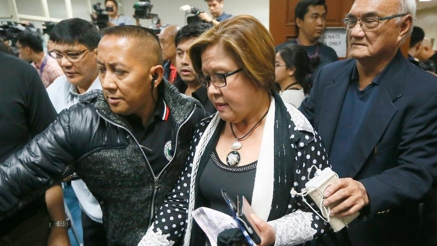 Opposition Senator Leila de Lima is escorted by Senate security to address the media after a warrant for her arrest was issued by a regional trial court Thursday, Feb. 23, 2017, in suburban Pasay city, south of Manila, Philippines. The Philippine court has issued an arrest warrant on drug charges for the senator and former top human rights official who is one of the most vocal critics of President Rodrigo Duterte and his deadly crackdown on illegal drugs. De Lima has vehemently denied the charges, which she says are part of Duterte's attempt to intimidate critics of his crackdown, which has left more than 7,000 drug suspects dead. (AP Photo/Bullit Marquez)