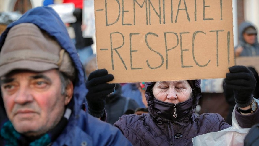 "FILE - In this Friday, Feb. 10, 2017 file photo a pro-government demonstrator holds a banner that reads ""Dignity - Respect"" during a protest outside the Romanian Presidency, in Bucharest, Romania. The sharp divide in Romanian society is a reflection of the different generations, pitting those who grew up, built a career and started a family under communism when the state provided cheap housing, health-care and jobs for everyone, against those who had their first vote when Romania was a decade into a free market economy and democratic reforms. (AP Photo/Vadim Ghirda, File)"