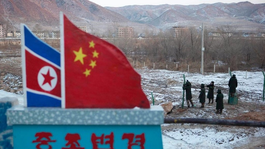 "FILE - In this Dec. 8, 2012, file photo, Chinese paramilitary policemen build a fence near a concrete marker depicting the North Korean and Chinese national flags with the words ""China North Korea Border"" at a crossing in the Chinese border town of Tumen in eastern China's Jilin province. China's announcement it has suspended North Korean coal imports may have been its first test of whether the Trump administration is ready to do something about a major, and mutual, security problem: North Korea's nukes. While China is Pyongyang's biggest enabler, it is also the biggest outside agent of regime-challenging change - just not in the way Washington has wanted. (AP Photo/Ng Han Guan, File)"