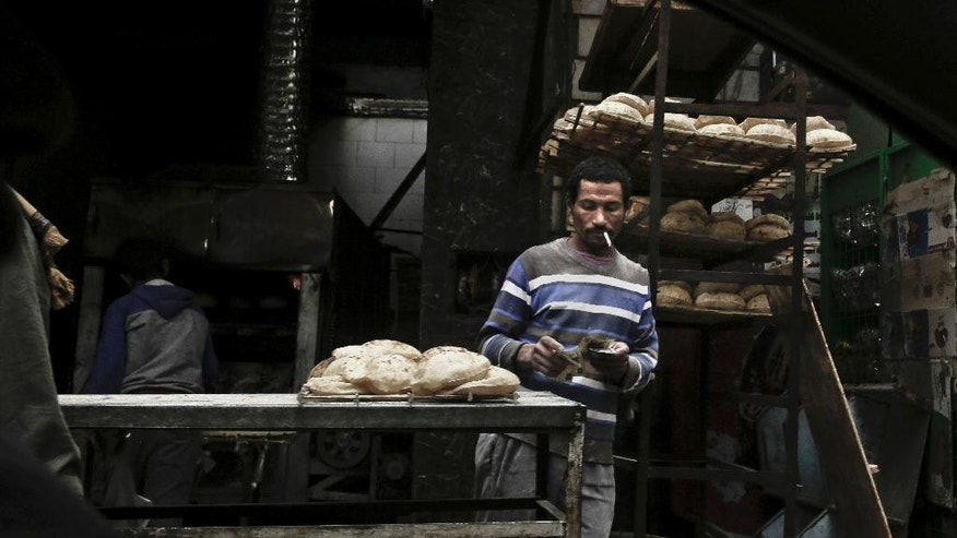 In this Tuesday, Feb. 14, 2017 photo, a vendor counts his money at a bread stand in the Sayeda Zeinab neighborhood of Cairo, Egypt. Egyptians are cutting spending and trying to make it through the country's worst inflation in a decade under President Abdel-Fattah el-Sissi's economic reforms. With inflation now nearing 30 percent _ and little public space for discontent _ they're finding they can do little else but bear down and hope the promised benefits of reform eventually come.  (AP Photo/Nariman El-Mofty)