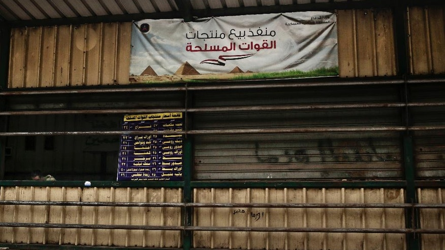 "In this Tuesday, Feb. 14, 2017 photo, an Egyptian solider sits near a list of product prices for sale and a banner with Arabic that reads, ""military products outlet for sale,"" in the Sayeda Zeinab neighborhood of Cairo, Egypt. Egyptians are cutting spending and trying to make it through the country's worst inflation in a decade under President Abdel-Fattah el-Sissi's economic reforms. With inflation now nearing 30 percent _ and little public space for discontent _ they're finding they can do little else but bear down and hope the promised benefits of reform eventually come.  (AP Photo/Nariman El-Mofty)"