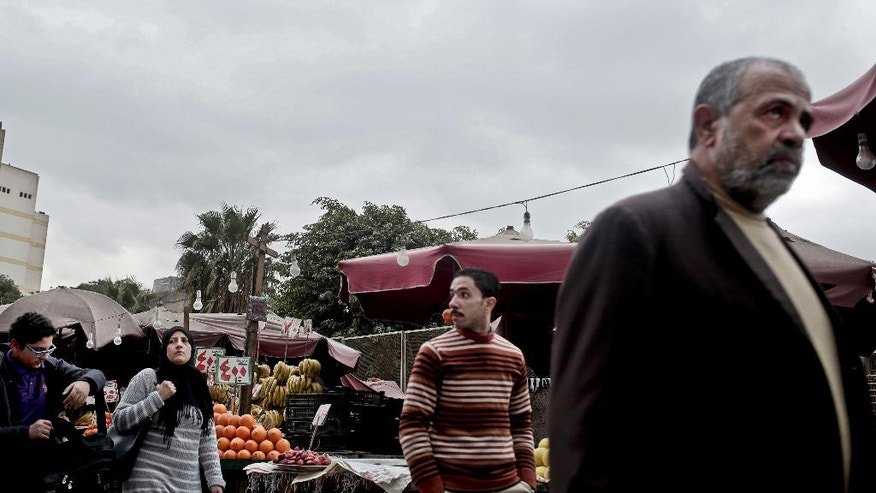 "In this Tuesday, Feb. 14, 2017 photo, people walk past a fruit market with prices on oranges that read, ""4 L.E. per kilogram,"" in the Sayeda Zeinab neighborhood of Cairo, Egypt. Egyptians are cutting spending and trying to make it through the country's worst inflation in a decade under President Abdel-Fattah el-Sissi's economic reforms. With inflation now nearing 30 percent _ and little public space for discontent _ they're finding they can do little else but bear down and hope the promised benefits of reform eventually come. (AP Photo/Nariman El-Mofty)"