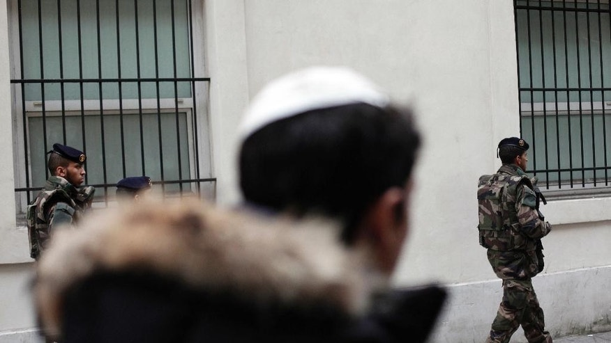 In this Jan. 13, 2015 file photo, French soldiers patrol next to a Jewish school, in Paris.  If far-right candidate Marine Le Pen wins upcoming presidential election, she plans to ban religious symbols from French streets, which would impact on  Jews who would no longer be allowed to wear their kippa head-coverings, and Muslims who would no longer be allowed to wear headscarfs in public which may dramatically alter the country's urban landscape. (AP Photo/Thibault Camus, File)