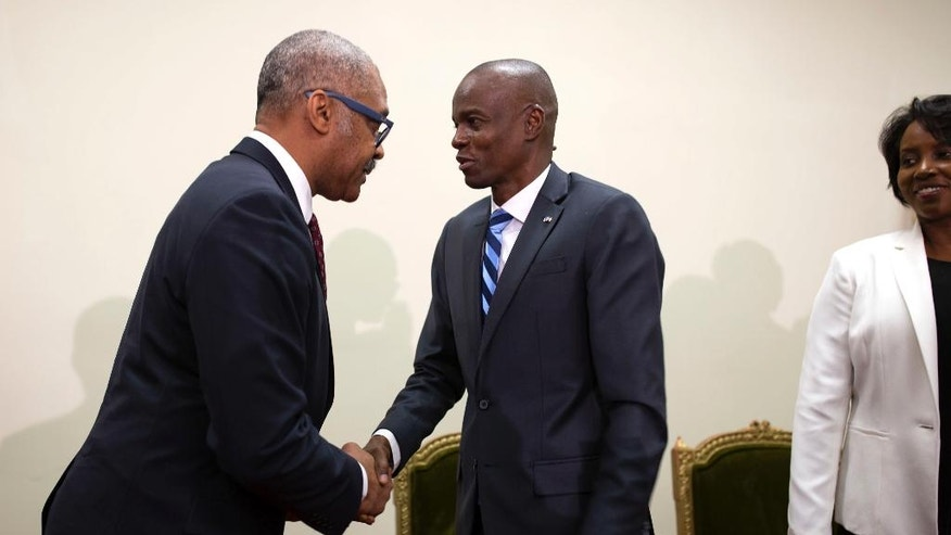 Haiti's President Jovenel Moise, right, shakes hands with Haiti's newly nominated Prime Minister Dr. Jack Guy Lafontant in Port-au-Prince, Haiti. Friday Feb. 24, 2017. Lafontant is a gastroenterologist and head of the Rotary Club in the commercial district of Petionville. (AP Photo/Dieu Nalio Chery)