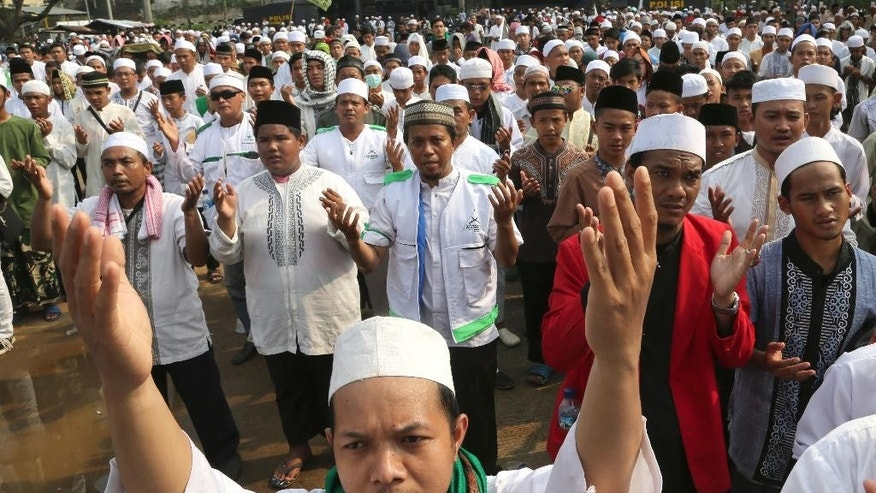 Muslim men pray during a protest outside the Ahmadiyah mosque in Depok, outside Jakarta, Indonesia, Friday. Feb. 24, 2016. The mosque has been shuttered by authorities after Muslim groups called for protests against the religious community they regard as heretical. (AP Photo/Tatan Syuflana)