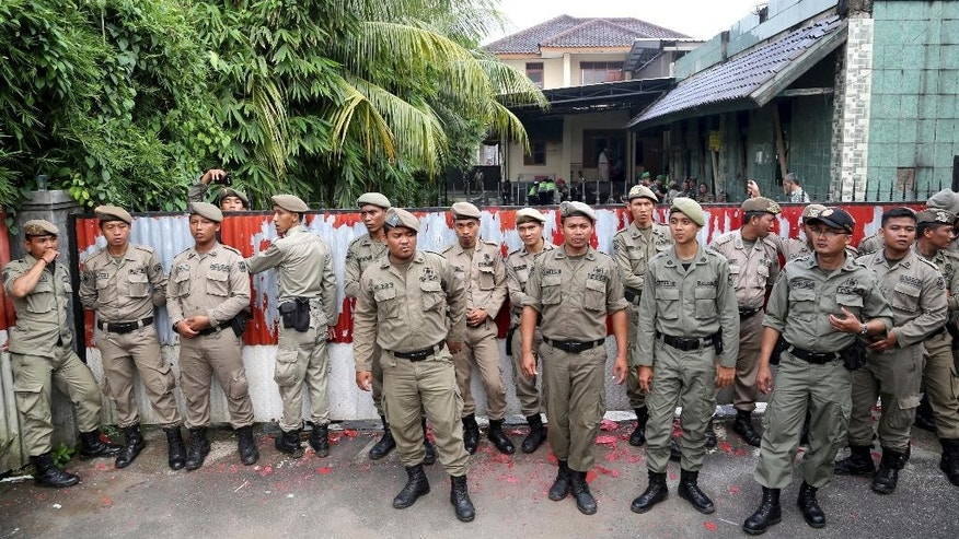 Government security officers stand guard outside the compound where the Ahmadiyah mosque is located in Depok, outisde Jakarta, Indonesia, Friday. Feb. 24, 2016. The mosque has been shuttered by authorities in Indonesia after Muslim groups called for protests against a minority they regard as heretical. (AP Photo/Tatan Syuflana)