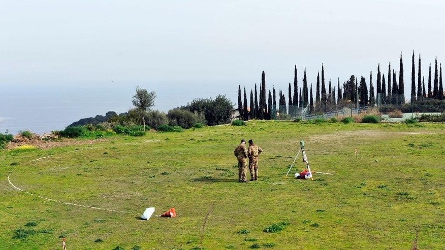 Italian soldiers take measurements at a site where a helicopter landing pands is supposed to be built, in the outskirts of Taormina, Italy, the host town of the upcoming May 26-27 G-7 summit, Friday, Feb. 24, 2017. Italy still needs to build two helicopter landing pads and repave miles of road, but Italian Government Undersecretary Maria Elena Boschi promised Friday that everything will be ready for the summit being held in the stunning Sicilian town overlooking the sea. (AP Photo/Salvatore Cavalli)