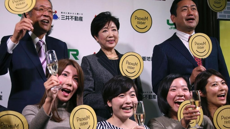 "Tokyo Gov. Yuriko Koike, center top, poses for photo with President of Mitsubishi Jisho Residence Hirotaka Sugiyama, top left and other office workers during a ""Premium Friday"" event in Tokyo Friday, Feb. 24, 2017. The event to mark the launching of ""Premium Friday,"" a joint project or concept endorsed by public and private sectors to promote work life balance as well as to revitalize economy by encouraging companies and workers to finish work at 1500 in the afternoon on every last Friday of the month. (AP Photo/Koji Sasahara)"