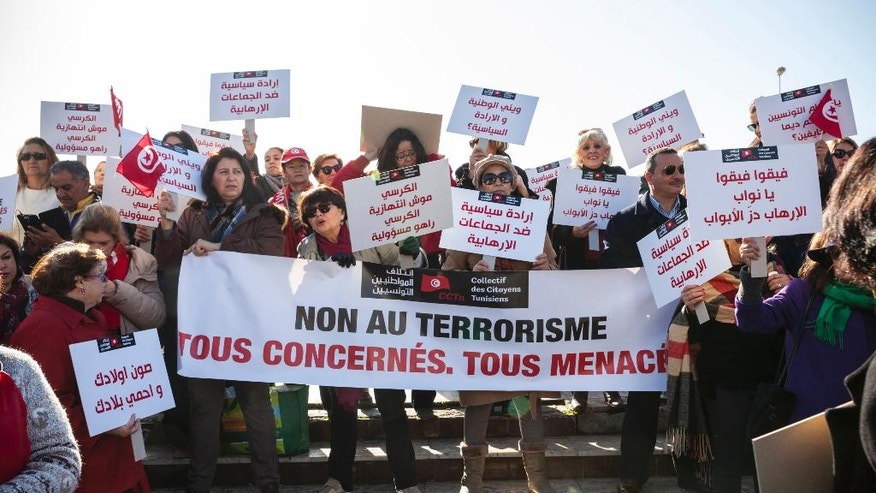 In this photo dated, Dec. 24, 2016, women demonstrate outside the Tunisian parliament, in Tunis, Saturday, Dec. 24, 2016, with banner reading : No to Terrorism. Tunisia has the dubious distinction of being one of the world's primary exporters of jihadi fighters, and now as extremists suffer defeats on the battlefield, many Tunisian people fear what will happen when  Jihadis return to this vulnerable country.(AP Photo/Ons Abid)