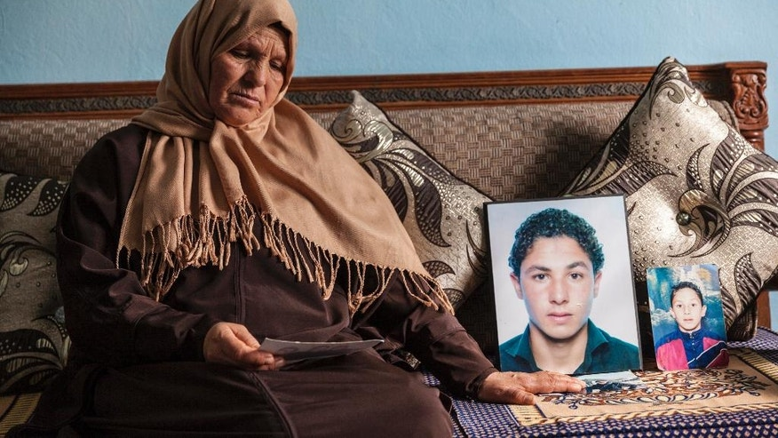 In this photo dated Thursday, Feb. 4, 2017, Rabia Farjallah, the mother of Mohamed Bel Hadj Amor, who was arrested by Syrian forces and jailed since 2012, poses next to a portrait of her son in Kelibia, Tunisia. Tunisia has the dubious distinction of being one of the world's primary exporters of jihadi fighters. Now, many fear they will return to a vulnerable country of backlogged courts and porous borders. (AP Photo/Ons Abid)