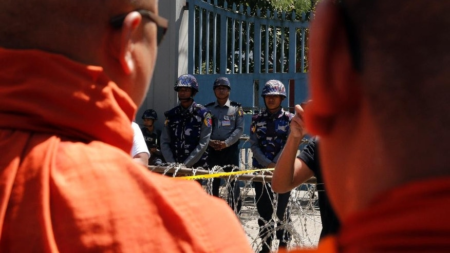 Myanmar police stand to provide security as Buddhist monks and people holding religious and National flags protest outside the Thailand embassy Friday, Feb.24, 2017, in Yangon, Myanmar. More than a hundred Buddhist monks and nationalists led a prayer and protest at the Thai Embassy Yangon on Friday to condemn the Thai government's ongoing raids on the Dhammakaya Temple in Bangkok, Thailand. (AP Photo/Thein Zaw)