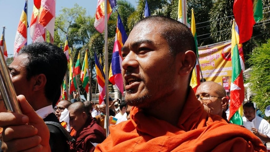 Buddhist monks and lay people holding banners, religious and National flags gather to march outside the Thailand Embassy, Friday, Feb. 24, 2017, in Yangon, Myanmar. More than a hundred monks and nationalists lead a prayer in protest at the Thai embassy in the country's commercial city Yangon on Friday to condemn the Thai government's ongoing raids on the Dhammakaya Temple in Bangkok. (AP Photo/Thein Zaw)