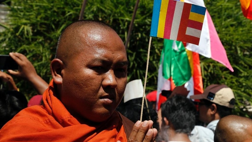 A Buddhist monk holding a religious flag prays as they protest outside the Thailand Embassy Friday, Feb. 24, 2017, in Yangon, Myanmar. More than a hundred Buddhist monks and nationalists led a prayer and protest at the Thai Embassy Yangon on Friday to condemn the Thai government's ongoing raids on the Dhammakaya Temple in Bangkok, Thailand. (AP Photo/Thein Zaw)