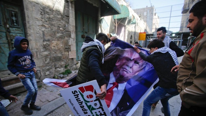 Palestinians tear down a poster of US President Donald Trump during a protest in the West Bank city of Hebron Friday, Feb.24, 2017. Trump is unpopular among Palestinians because he has broken from his predecessor and adopted friendlier positions to the Israeli government and a vaguer stance on Palestinian statehood.  (AP Photo/Nasser Shiyoukhi).