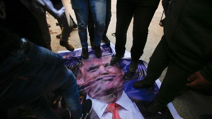 Palestinians throw shoes at a poster of US President Donald Trump during a protest in the West Bank city of Hebron Friday, Feb.24, 2017. Trump is unpopular among Palestinians because he has broken from his predecessor and adopted friendlier positions to the Israeli government and a vaguer stance on Palestinian statehood.  (AP Photo/Nasser Shiyoukhi).