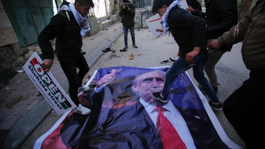 Palestinians step ona poster of US President Donald Trump during a protest in the West Bank city of Hebron Friday, Feb.24, 2017. Trump is unpopular among Palestinians because he has broken from his predecessor and adopted friendlier positions to the Israeli government and a vaguer stance on Palestinian statehood.  (AP Photo/Nasser Shiyoukhi).