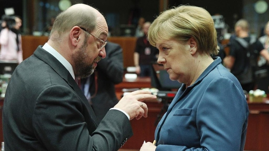 FILE - In this Dec. 19, 2013 photo then European Parliament President Martin Schulz, left, talks with German Chancellor Angela Merkel, during an EU summit at the European Council building in Brussels. A new poll published Friday, Feb. 24, 2017 shows Germany's center-left Social Democrats nudging past Chancellor Angela Merkel's conservative bloc in support for the first time in more than a decade. (AP Photo/Yves Logghe, file)