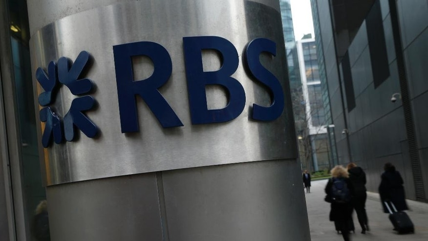FILE - This is a Thursday, Jan. 26, 2017 file photo of People as they  walk past one of the headquarters buildings showing the logo of the Royal Bank of Scotland in London. Royal Bank of Scotland has posted nine consecutive years of losses after the taxpayer-owned group set aside another 4 billion pounds ($5 billion) in the fourth quarter of 2016 to cover the costs of misconduct during the financial crisis and targeted a return to profitability in 2018. (AP Photo/Alastair Grant/File)