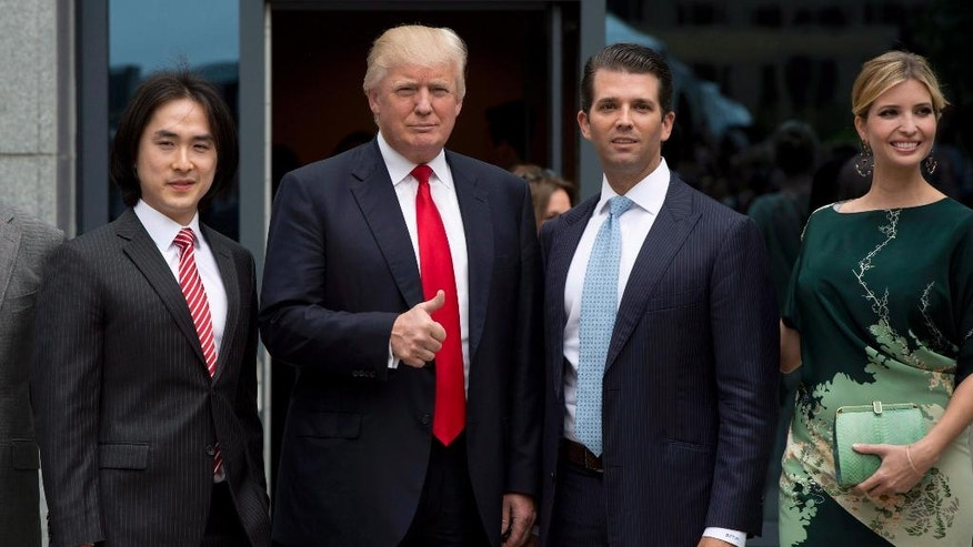 In this June 19, 2013 photo, Donald Trump, center, gives the thumbs up as he arrives with son Donald Trump Jr., daughter Ivanka Trump and Joo Kim Tiah, CEO and president of Holborn Group, to announce the building of Trump International Hotel and Tower Vancouver in downtown Vancouver, British Columbia, Canada. The 69-story tower has drawn praise for its sleek, twisting design. Prices for the condominiums have set records. But the politics of President Donald Trump have caused such outrage that the mayor won't attend the Feb. 28 grand opening and has lobbied for a name change. (Jonathan Hayward/The Canadian Press via AP)