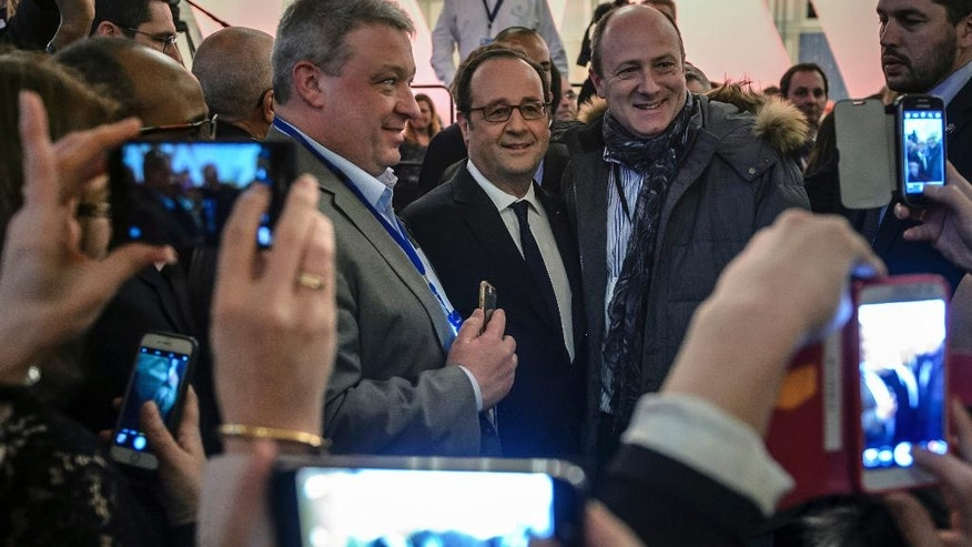 French President Francois Hollande is photographed by Disney cast members at the Disneyland Paris theme parks in Marne-la-Vallee, north of Paris, Saturday Feb. 25, 2017. Hollande visited Disneyland Paris to mark its 25th anniversary, as Europe's most popular tourist attraction struggles with long-running financial challenges. (Christophe Petit Tesson/Pool photo via AP)