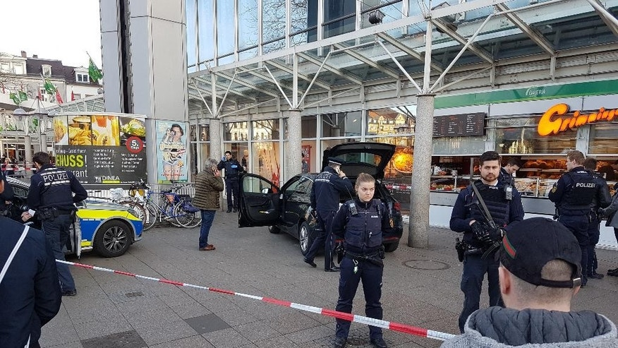 A car stands in front of a store, guarded by police in Heidelberg, Germany, Saturday, Feb. 25, 2017. A man apparently drove a car into pedestrians in a central square in the city of Heidelberg, injuring three people, then fled and was shot after being tracked down by officers, police said. (R. Priebe/PR-Video/dpa via AP)