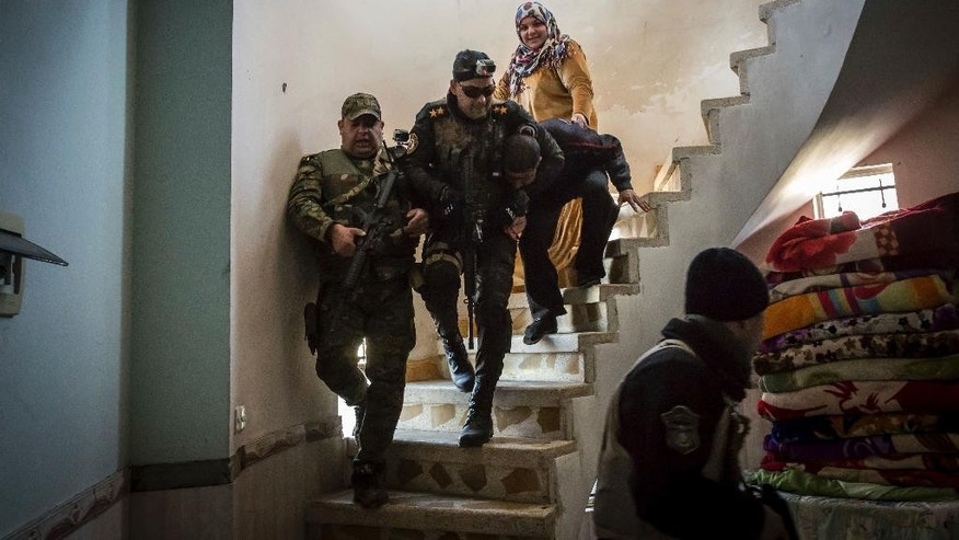 "FILE - In this Tuesday, Feb. 21, 2017 file photo, Iraqi security forces drag a suspected Islamic State group fighter down a spiral staircase after raiding his house in the liberated eastern part of Mosul. The suspects are identified via intelligence gathered from information received from other civilians in the city. A secretive Iraqi intelligence unit is leading the hunt for IS sleeper cells in liberated Mosul. As Iraqi forces secure territorial victories in Mosul's west, in the city's east, an area declared ""fully liberated"" in January, Iraqi intelligence officials estimate dozens of IS fighters and sympathizers have remained in the more than 60 square kilometers of dense urban neighborhoods. (AP Photo/John Beck, File)"