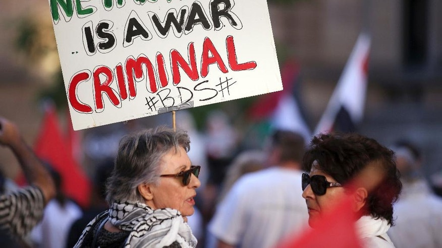 A woman holds a placard as members of the Palestinian community and their supporters gather to rally against a state visit of Israeli Prime Minister Benjamin Netanyahu in Sydney, Thursday, Feb. 23, 2017. Netanyahu is on a four-day visit to Australia. (AP Photo/Rick Rycroft)