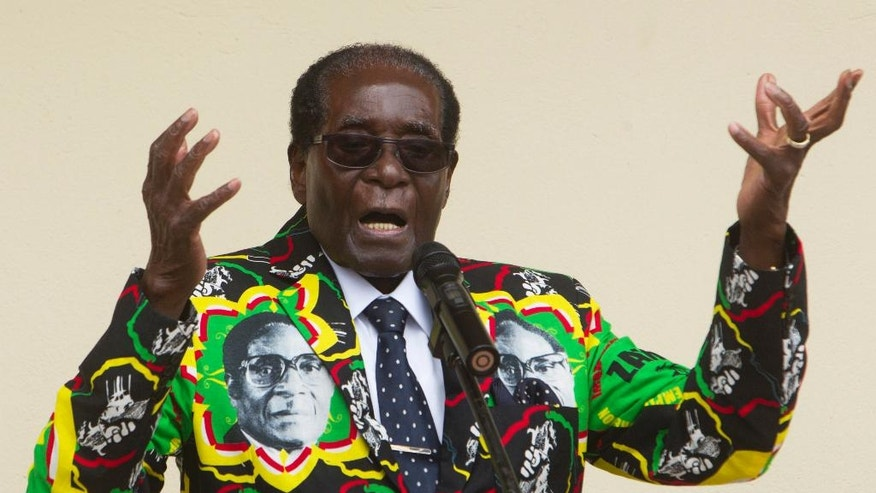 FILE - In this Dec, 17, 2016, file photo, Zimbabwean President Robert Mugabe addresses people at an event before the closure of his party's 16th Annual Peoples Conference in Masvingo, south of Harare. Zimbabwe. Mugabe is celebrating his 93rd birthday on Saturday, Feb. 25, 2017 amid granite hills where ancient spirits are said to dwell, defying calls to resign after nearly four decades in power in a region known for opposing a leader who says he'll run again in 2018 elections. (AP Photo/Tsvangirayi Mukwazhi, File)