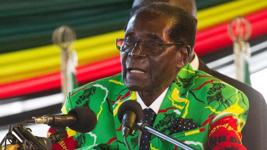 FILE - In this Dec. 17, 2016, file photo, Zimbabwean President Robert Mugabe addresses people during the closure of his party's 16th Annual Peoples Conference in Masvingo, south of Harare, Zimbabwe. Zimbabwe. Mugabe is celebrating his 93rd birthday on Saturday, Feb. 25, 2017 amid granite hills where ancient spirits are said to dwell, defying calls to resign after nearly four decades in power in a region known for opposing a leader who says he'll run again in 2018 elections. (AP Photo/Tsvangirayi Mukwazhi, File)