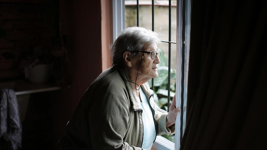 This Feb. 13, 2017 photo shows Maria Antonieta Lobos, whose son died fighting in the Falkland war, looking outside her window in Buenos Aires, Argentina. Lobos says she has never been able to properly mourn Jose Antonio, who died June 14, 1982, the last day of the war between Argentina and Britain over the archipelago, because she doesn't know which remains are his. (AP Photo/Victor R. Caivano)