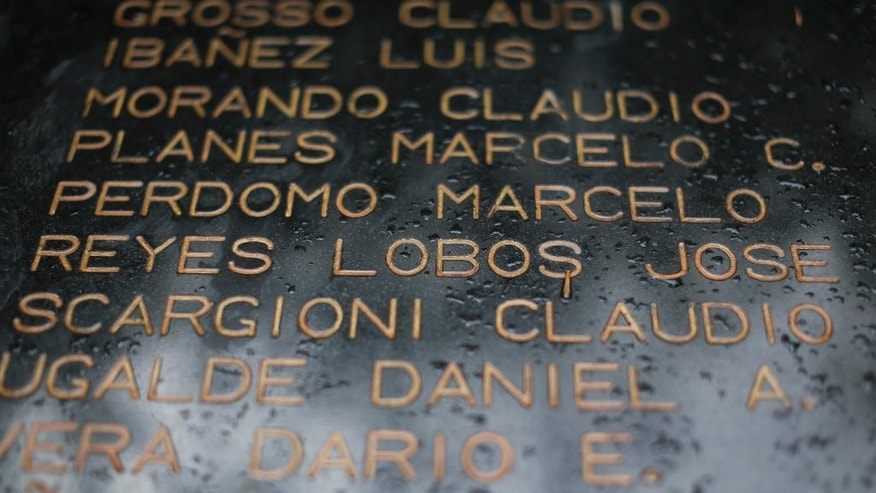 This Feb. 13, 2017 photo shows a plaque with the names of Argentine soldiers who died in the Falklands war, including Jose Antonio Lobos whose remains have not been identified, in a plaza near the Lobos' family home in Buenos Aires, Argentina. Under an agreement signed in December by Argentina and Britain, the International Committee of the Red Cross has begun the process of putting a name to each of the soldiers buried in Darwin Military Cemetery in the Falkland Islands. (AP Photo/Victor R. Caivano)