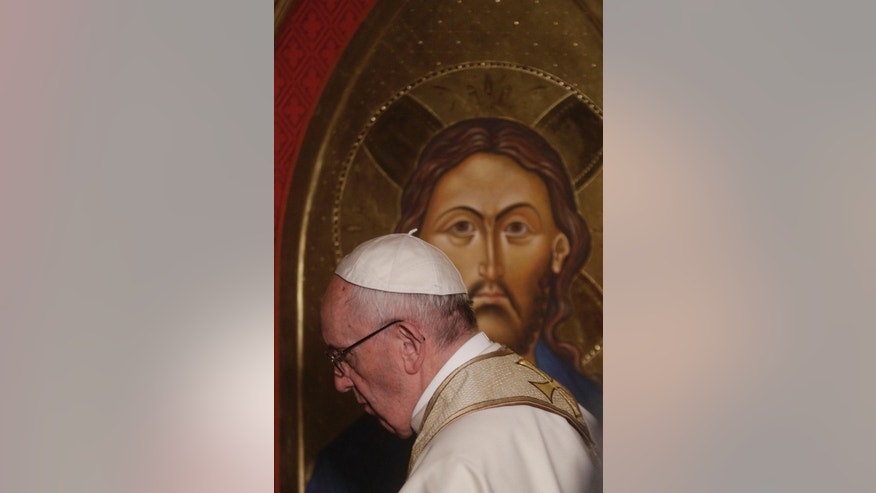 Pope Francis passes in front of an icon of Christ the Saviour by English artist Ian Knowles during his historic visit to the Anglican Church of All Saints in Rome, Sunday, Feb. 26, 2017. (AP Photo/Gregorio Borgia)