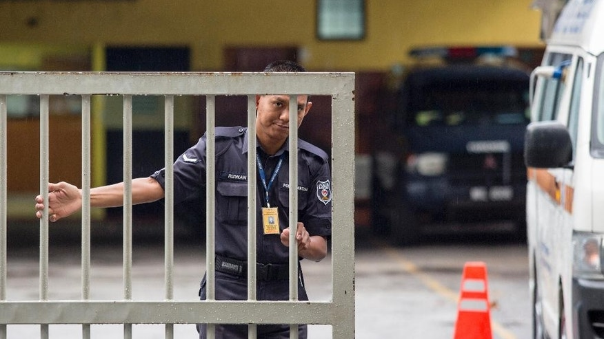 A Malaysian police officer closes the gate of the National Forensic Institute at Kuala Lumpur Hospital in Kuala Lumpur, Malaysia, Sunday, Feb. 26, 2017. Malaysian police ordered a sweep of Kuala Lumpur airport for toxic chemicals and other hazardous substances following the killing of Kim Jong Nam. (AP Photo/Alexandra Radu)