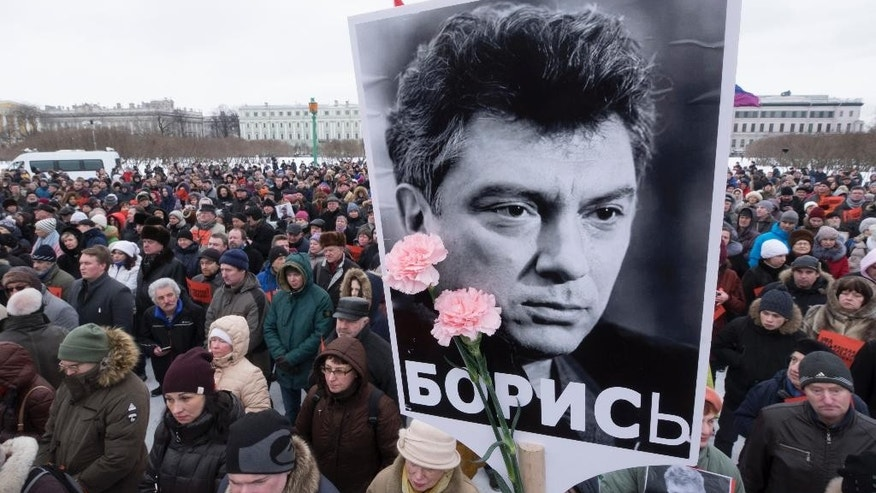 People gather in memory of opposition leader Boris Nemtsov, portrait in center, in St. Petersburg, Russia, Sunday, Feb. 26, 2017. Russians have taken to the streets of downtown Moscow and St. Petersburg to mark two years since Nemtsov was gunned down outside the Kremlin. (AP Photo/Dmitri Lovetsky)