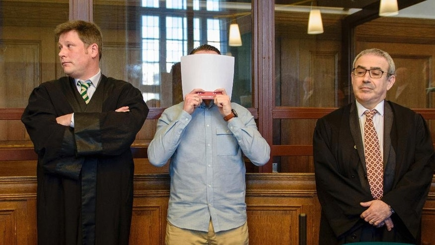 Accused Hamdi H., no full name given in line with Germany's privacy laws, covers his face before his verdict in a court in Berlin, Monday, Feb. 27, 2017, before he was sentenced for a life-term sentence for murder after killing a pedestrian when taking part in an illegal car race in downtown Berlin. (Gregor Fischer/dpa via AP)