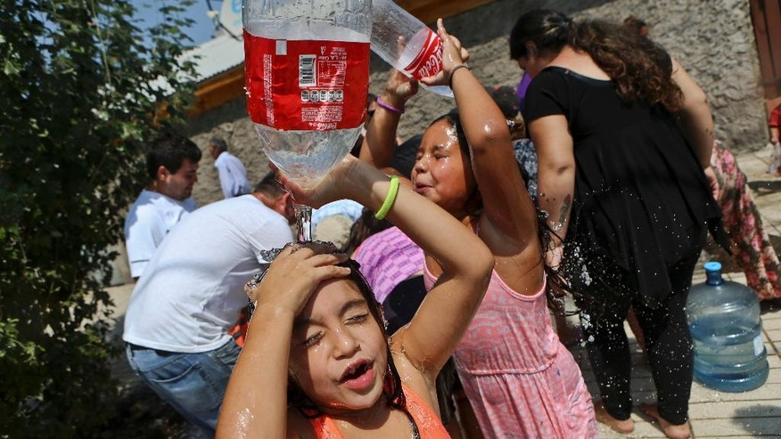 Two girls refresh themselves while residents gather water from a fire hydrant at a neighborhood in Santiago, Chile, Monday, Feb. 27, 2017. Millions are without potable water in Santiago's greater metropolitan area after floods and mudslides cut supplies. (AP Photo/ Esteban Felix)