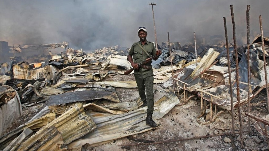 A Somali soldier walks through the wreckage after a fire engulfed the Somali capital's main market in Mogadishu, Monday, Feb. 27, 2017. A police officer said the overnight inferno was moved by winds which started at the gold bazaar and rapidly spread into different areas of the market, razing large buildings, shops and food stores. (AP Photo/Farah Abdi Warsameh)