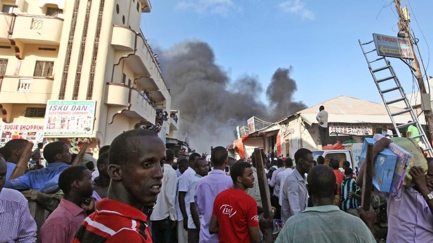 Somali traders watch as their stores burn, after a fire engulfed the Somali capital's main market in Mogadishu, Monday, Feb. 27, 2017. A police officer said the overnight inferno was moved by winds which started at the gold bazaar and rapidly spread into different areas of the market, razing large buildings, shops and food stores. (AP Photo/Farah Abdi Warsameh)