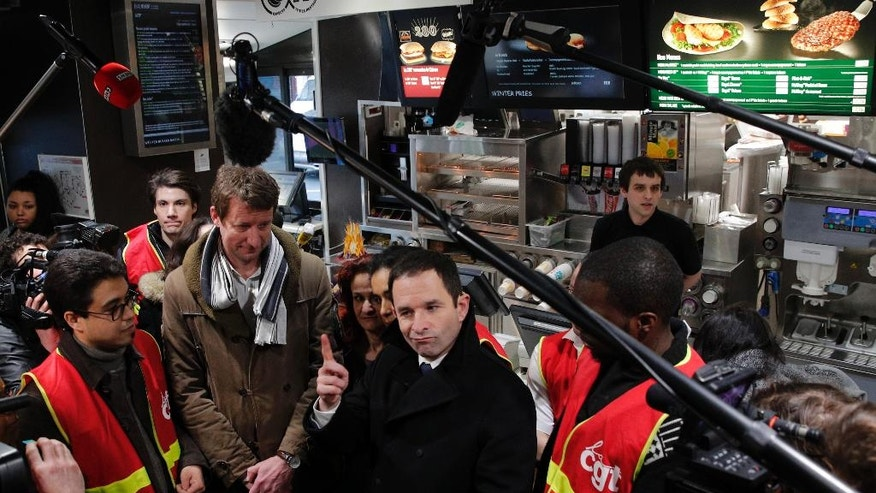 Candidate for the French left's presidential election, Benoit Hamon, center, speaks to journalists next to former presidential candidate for the Green Party Europe-Ecologie-Les Verts (EELV) Yannick Jadot, center left, as they meet unionists of the General Confederation of Labour (CGT) at a fast-food restaurant, in Paris, Monday, Feb. 27, 2017. (AP Photo/Christophe Ena)