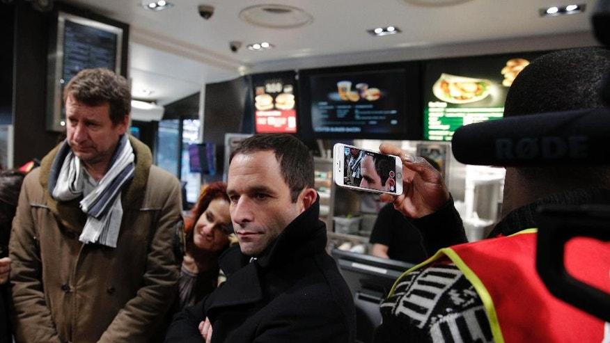 Candidate for the French left's presidential election, Benoit Hamon, center, speaks to journalists next to former presidential candidate for the Green Party Europe-Ecologie-Les Verts (EELV) Yannick Jadot, left, as they meet unionists of the General Confederation of Labour (CGT) at a fast-food restaurant, in Paris, Monday, Feb. 27, 2017. (AP Photo/Christophe Ena)