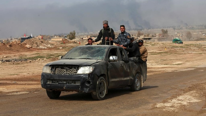 Iraqi forces advance during fighting against Islamic State militants, in western Mosul, Iraq, Monday, Feb. 27. 2017. A senior Iraqi police commander said Monday that troops have taken control of the western side of a key bridge in Mosul amid intense clashes with the Islamic State group. The commander of the Federal Police Rapid Response Force, said his forces pushed into Mosul's western Gawsaq neighborhood Monday, reaching the foot of what's known locally as the 4th Bridge.